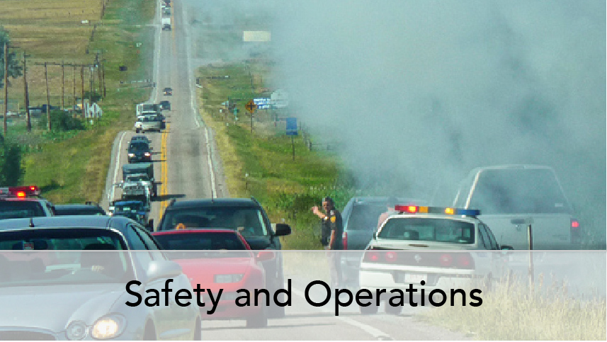 WTI Program Thumb Safety and Operations. Image of vehicles backed up on rural road at site of crash. Enforcement vehicle and traffic management.
